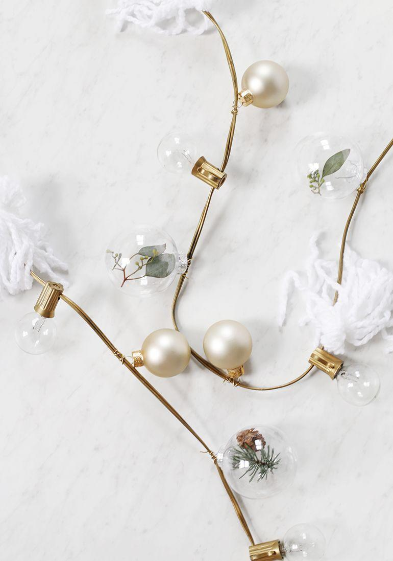 """<p>Spruce up a standard string of lights with a series of frosted ornaments, eucalyptus-filled ornaments, and yarn tassels. </p><p><a href=""""https://themerrythought.com/diy/diy-string-lights-garland/"""" rel=""""nofollow noopener"""" target=""""_blank"""" data-ylk=""""slk:Get the tutorial."""" class=""""link rapid-noclick-resp"""">Get the tutorial.</a></p><p><a class=""""link rapid-noclick-resp"""" href=""""https://www.amazon.com/Metaku-Operated-Waterproof-Decorative-Christmas/dp/B07XBZ4PBJ?tag=syn-yahoo-20&ascsubtag=%5Bartid%7C10072.g.37499128%5Bsrc%7Cyahoo-us"""" rel=""""nofollow noopener"""" target=""""_blank"""" data-ylk=""""slk:SHOP LIGHTS"""">SHOP LIGHTS</a></p>"""