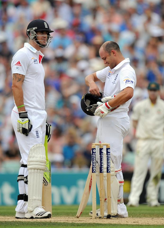 England's Jonathan Trott (right) repairs his helmet after being struck on the head during day three of the Fifth Investec Ashes Test match at The Kia Oval, London.