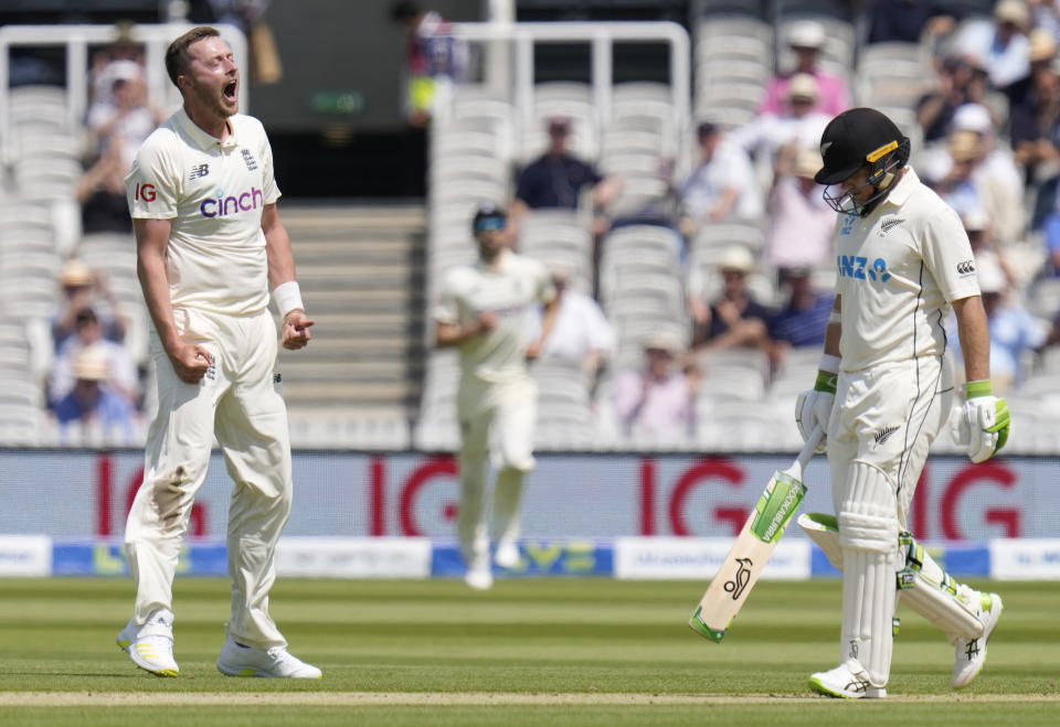 England's Ollie Robinson, left, celebrates taking the wicket of New Zealand's Tom Latham, right, during the first day of the Test match between England and New Zealand at Lord's cricket ground in London, Wednesday, June 2, 2021. (AP Photo/Kirsty Wigglesworth)