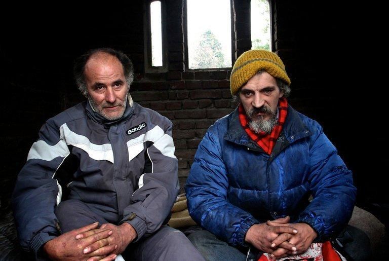 Homeless men Bratislav Jovanovic (R), 43, and Aleksandar Dejic, 50, sit on January 10, 2013 inside a tomb at a cemetery in Nis, Serbia. Both men have been homeless for nearly twenty years, since they lost their family members