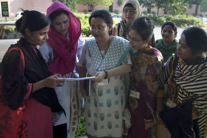 Pakistani doctor Anita Zaidi, center, who heads the pediatrics department at the Aga Khan University, shows a project plan to her colleagues at a university in Karachi, Pakistan, Tuesday, Dec. 10, 2013. She has won a $1 million grant to fight early child mortality in a small fishing village in southern Pakistan in a contest financed by an American entrepreneur to find innovative ways to save lives, the Caplow Children's Prize announced Tuesday. (AP Photo/Shakil Adil)