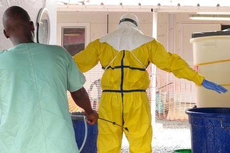 A health worker gets sprayed with disinfectant in an Ebola virus treatment center in Conakry