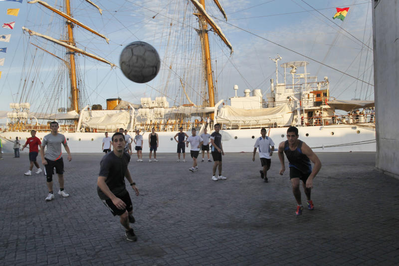 Crew members play soccer next to the three-masted ARA Libertad, a symbol of Argentina's navy, as it sits docked at the Tema port, outside Accra, Ghana, Saturday, Oct. 20, 2012. Argentina announced the immediate evacuation Saturday of about 300 crew members from the Libertad, a navy training ship seized in Africa nearly three weeks ago as collateral for unpaid bonds dating from the South American nation's economic crisis a decade ago.(AP Photo/Gabriela Barnuevo)