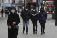Pedestrians wear masks as they walk on Oxford Street in London, Saturday, Dec. 26, 2020. London is currently in Tier 4 with all non essential retail shops closed and people have been asked to stay at home, on what is usually one of the busiest retail days of the year with the traditional Boxing Day sales in shops. (AP Photo/Kirsty Wigglesworth)