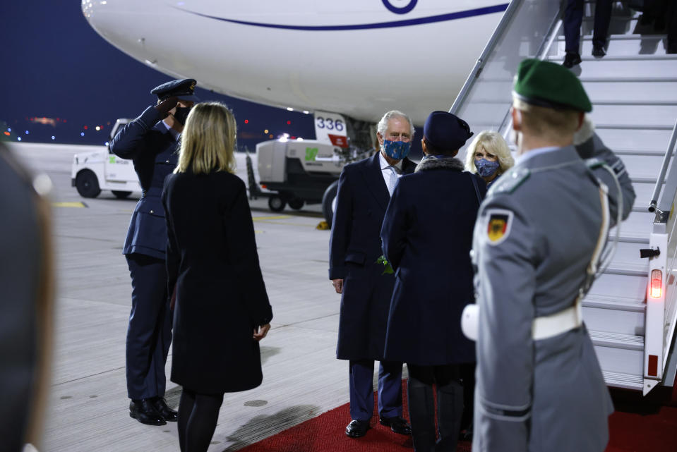 Britain's Prince Charles, center, and his wife Camilla, Duchess of Cornwall, center right, exit their plane as they arrive at Berlin Brandenburg Airport, Germany, Saturday Nov. 14, 2020. (Odd Andersen/Pool via AP)