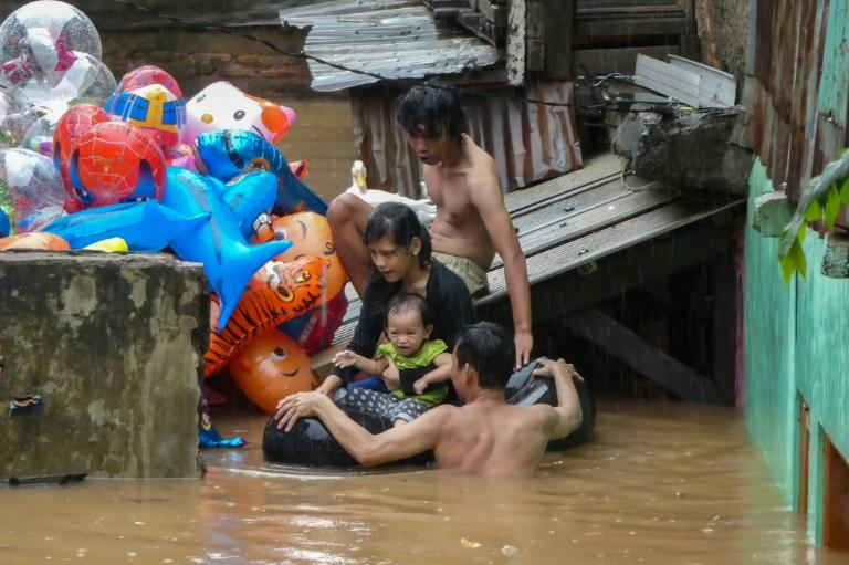 A family evacuates their home after heavy rain caused widespread flooding in Jakarta