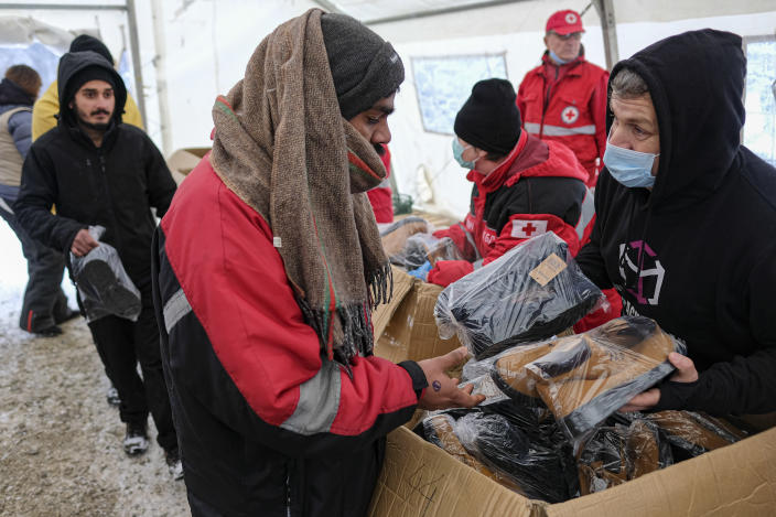 Migrants receive footwear and blankets from a humanitarian organization at the Lipa camp, outside Bihac, Bosnia, Monday, Jan. 11, 2021. Aid workers say migrants staying at a camp in northwestern Bosnia have complained or respiratory and skin diseases after spending days in make-shift tents and containers amid freezing weather and snow blizzards. Most of the hundreds of migrants at the Lipa facility near Bosnia's border with Croatia on Monday have been accommodated in heated military tents following days of uncertainty after a fire gutted most of the camp on Dec. 23. (AP Photo/Kemal Softic)