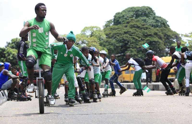 Men form a human chain led by a man on a monocycle, during an event to mark Nigeria independence day, in Lagos, Nigeria. Tuesday, Oct. 1, 2013 . Nigeria marked 53 years of independence Tuesday with little to celebrate: scores of families are in mourning over killings by suspected Islamic extremists, security forces on high alert against feared bomb attacks and the government rift by an internal power struggle. (AP Photo/Sunday Alamba)