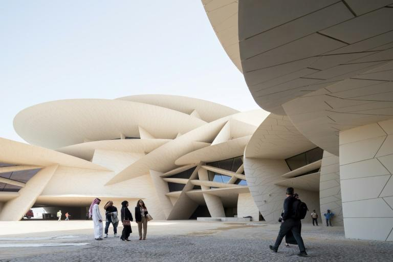 Visitors walk in front of the newly constructed National Museum of Qatar, which opens this week