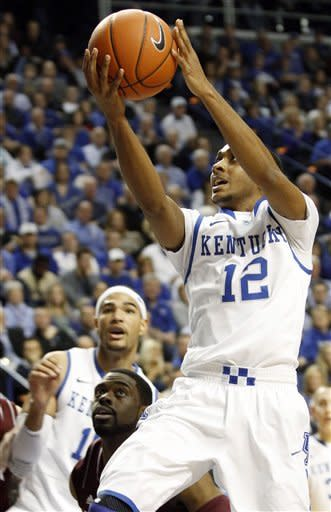 Kentucky's Ryan Harrow (12) shoots next to Mississippi State's Tyson Cunningham and Kentucky's Willie Cauley-Stein, rear, during the first half of an NCAA college basketball game at Rupp Arena in Lexington, Ky., Wednesday, Feb. 27, 2013. (AP Photo/James Crisp)