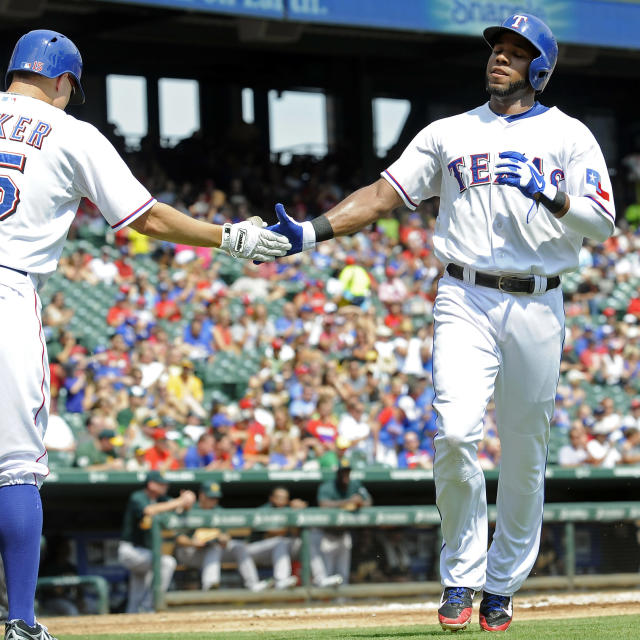 Texas Rangers' Elvis Andrus, right, is congratulated at home plate by Jeff Baker after scoring a run in the first inning of a baseball game against the Oakland Athletics, Sunday, Sept. 15, 2013, in Arlington, Texas. (AP Photo/Matt Strasen)