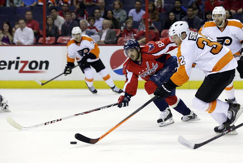 Philadelphia Flyers defenseman Mark Streit (32), from Switzerland, skates with the puck as he is defended by Washington Capitals center Mathieu Perreault (85) in the first period of a preseason NHL hockey game on Friday, Sept. 27, 2013, in Washington. (AP Photo/Alex Brandon)