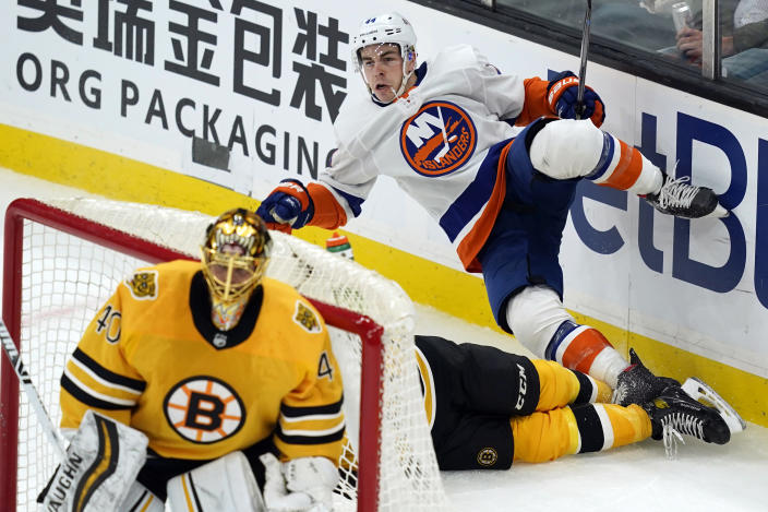 New York Islanders center Jean-Gabriel Pageau (44) trips over Boston Bruins defenseman Charlie McAvoy (73) as Bruins goaltender Tuukka Rask (40) guards the net in the second period of an NHL hockey game, Thursday, April 15, 2021, in Boston. (AP Photo/Elise Amendola)