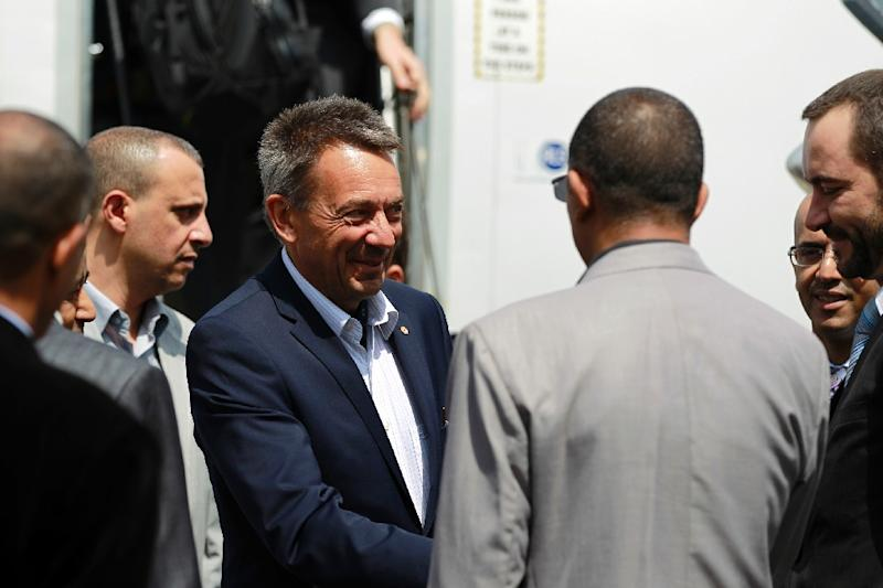 Peter Maurer (C), president of the International Committee of the Red Cross, is welcomed upon his arrival at Sanaa International Airport on August 8, 2015 (AFP Photo/Mohammed Huwais)