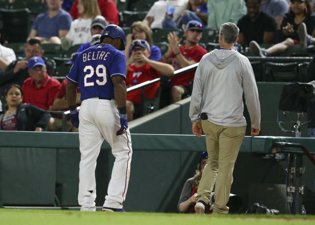 Texas Rangers' Adrian Beltre walks off the field with athletic trainer Kevin Harmon, right, after suffering a leg injury running out a run-scoring single against the Oakland Athletics in the eighth inning of a baseball game Tuesday, April 24, 2018, in Arlington, Texas. Beltre did not return in the game. (AP Photo/Richard W. Rodriguez)