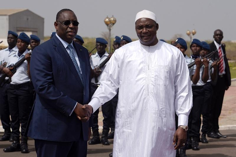 Senegalese president Macky Sall (L) shakes hands with his Gambian counterpart Adama Barrow upon his arrival at Dakar airport for a three-day official visit to Senegal, on March 2, 2017