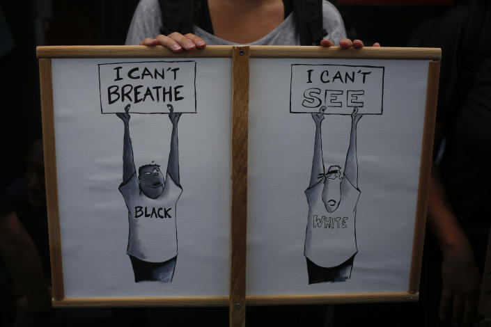 A person holds a placard during a march against police brutality and racism in Paris, France, Saturday, June 13, 2020, organized by supporters of Adama Traore, who died in police custody in 2016 in circumstances that remain unclear despite four years of back-and-forth autopsies. The march was expected to be the biggest of several demonstrations Saturday inspired by the Black Lives Matter movement in the U.S., and French police ordered the closure of freshly reopened restaurants and shops along the route fearing possible violence. (AP Photo/Thibault Camus)