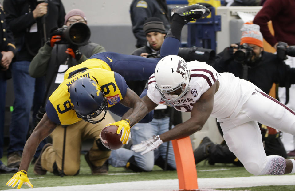 West Virginia safety KJ Dillon (9) dives into the end zone ahead of Texas A&M running back Tra Carson, right, as Dillon runs a pass interception back 35 yards for a touchdown in the first half of the Liberty Bowl NCAA college football game, Monday, Dec. 29, 2014, in Memphis, Tenn. (AP Photo/Mark Humphrey)