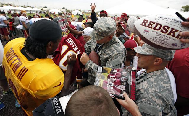 Washington Redskins quarterback Robert Griffin III, left, signs an autograph for a fan after practice at the team's NFL football training facility, Sunday, July 27, 2014, in Roanoke, Va. (AP Photo/Alex Brandon)