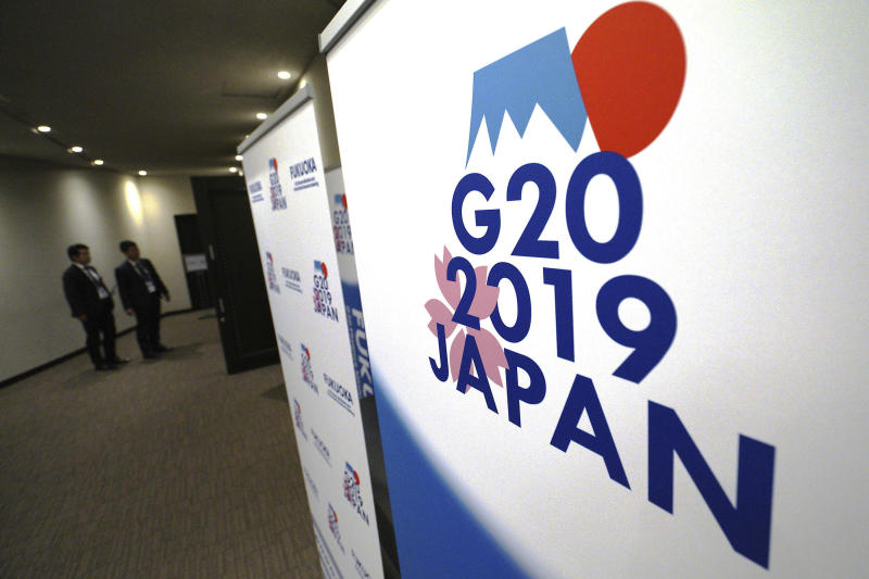 FILE - In this June 7, 2019, file photo, staff members stand near the emblem of G20 2019 Japan at the entrance of the press center of G20 Finance Ministers' and Central Bank Governors' Meeting in Fukuoka, western Japan. Chinese and U.S. trade negotiators are in contact on ways of resolving disputes ahead of an expected meeting between their heads of state at the G-20 summit in Japan later this week, a Chinese official said Monday, June 24, 2019. (AP Photo/Eugene Hoshiko, File)