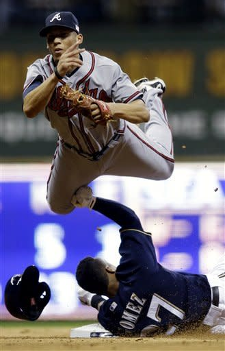 **RESENT WITH ALTERNATE CROP** Atlanta Braves' Andrelton Simmons leaps over Milwaukee Brewers' Carlos Gomez (27) as he tries to turn a double play on a ball hit by Jean Segura during the seventh inning of a baseball game Tuesday, Sept. 11, 2012, in Milwaukee. Segura beat the throw. (AP Photo/Morry Gash)