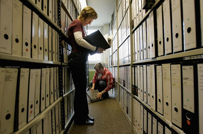 Employees of the ITS (International Tracing Service) research documents at the Holocaust Archive on April 28, 2006 in Bad Arolsen, Germany. (Photo by Ralph Orlowski/Getty Images)