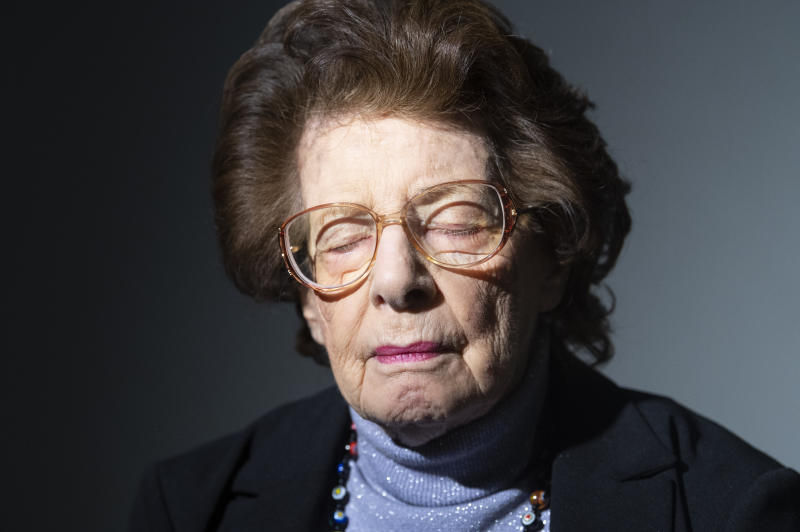 In this hursday, Jan. 16, 2020 photo Auschwitz survivor Agi Geva poses for a photo at the United States Holocaust Memorial Museum in Washington. Ahead of commemorations marking the 75th anniversary of the liberation of Auschwitz by the Soviet army, Associated Press reporters and photographers visited survivors in Germany, Poland, Sweden, Russia, the United States and Israel. Many posed showing the blue tattoos still imprinted on their arms, lifelong testaments of their suffering and loss. (AP Photo/Kevin Wolf)