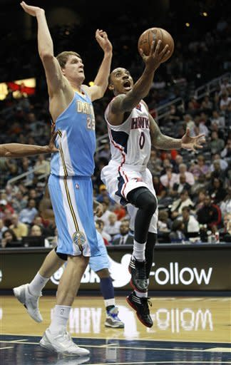 Atlanta Hawks point guard Jeff Teague (0) drives to the basket as Denver Nuggets center Timofey Mozgov (25) defends during the first half of an NBA basketball game on Wednesday, Dec. 5, 2012. (AP Photo/John Bazemore)
