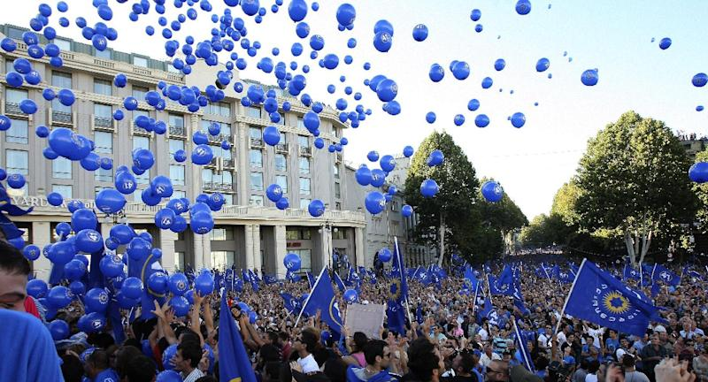 Opposition supporters hold their party flags and release balloons during a rally in the center of Georgia's capital Tbilisi, Saturday, Sept. 29, 2012,  in a show of strength days ahead of a parliamentary election that presents the toughest challenge to the future of Mikhail Saakashvili's government since he became president nearly nine years ago. Georgia holds tightly contested parliamentary elections on Oct. 1. (AP Photo/Shakh Aivazov)