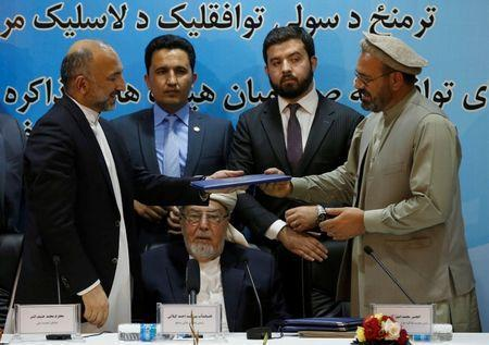 Mohammad Amin Karim (R), representative of Gulbuddin Hekmatyar, and Afghanistan national security adviser Mohammad Hanif Atmar (L) hold a document after signing a peace deal in Kabul, Afghanistan, September 22, 2016. REUTERS/Omar Sobhani - RTSOXFU