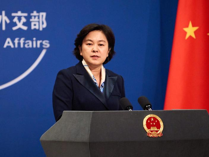 The Chinese Foreign Ministry spokesperson Hua Chunying stands at a podium in front of a Chinese flag.