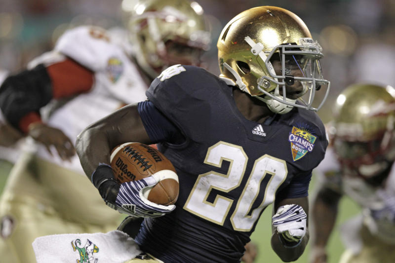 FILE - In this Dec. 29, 2011, file photo, Notre Dame's Cierre Wood gains yardage against Florida State during the second half of the Champs Sports Bowl NCAA college football game in Orlando, Fla. Notre Dame running backs Theo Riddick and Wood would like to get the ball a little more often. Coach Brian Kelly thinks he needs to get the ball to George Atkinson III more often. The three backs, though, say they are all friends and cheer one another. (AP Photo/John Raoux, File)