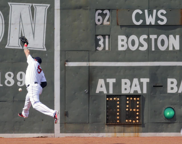 Boston Red Sox left fielder Jonny Gomes leaps but can't make the play on a double by Chicago White Sox' Jose Abreu during the first inning of a baseball game at Fenway Park in Boston, Thursday, July 10, 2014. (AP Photo/Charles Krupa)