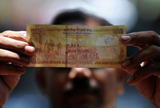 A shopkeeper holds a 500 rupee note as he inspects it for authenticity