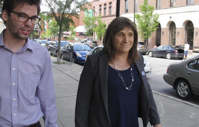 In this Aug. 9, 2018 photo, Christine Hallquist, transgender candidate seeking the Democratic party nomination to run for governor of Vermont, walks with campaign aide David Glidden in Burlington, Vt. Vermont's state primary election is scheduled for Tuesday, Aug. 14. (AP Photo/Wilson Ring)