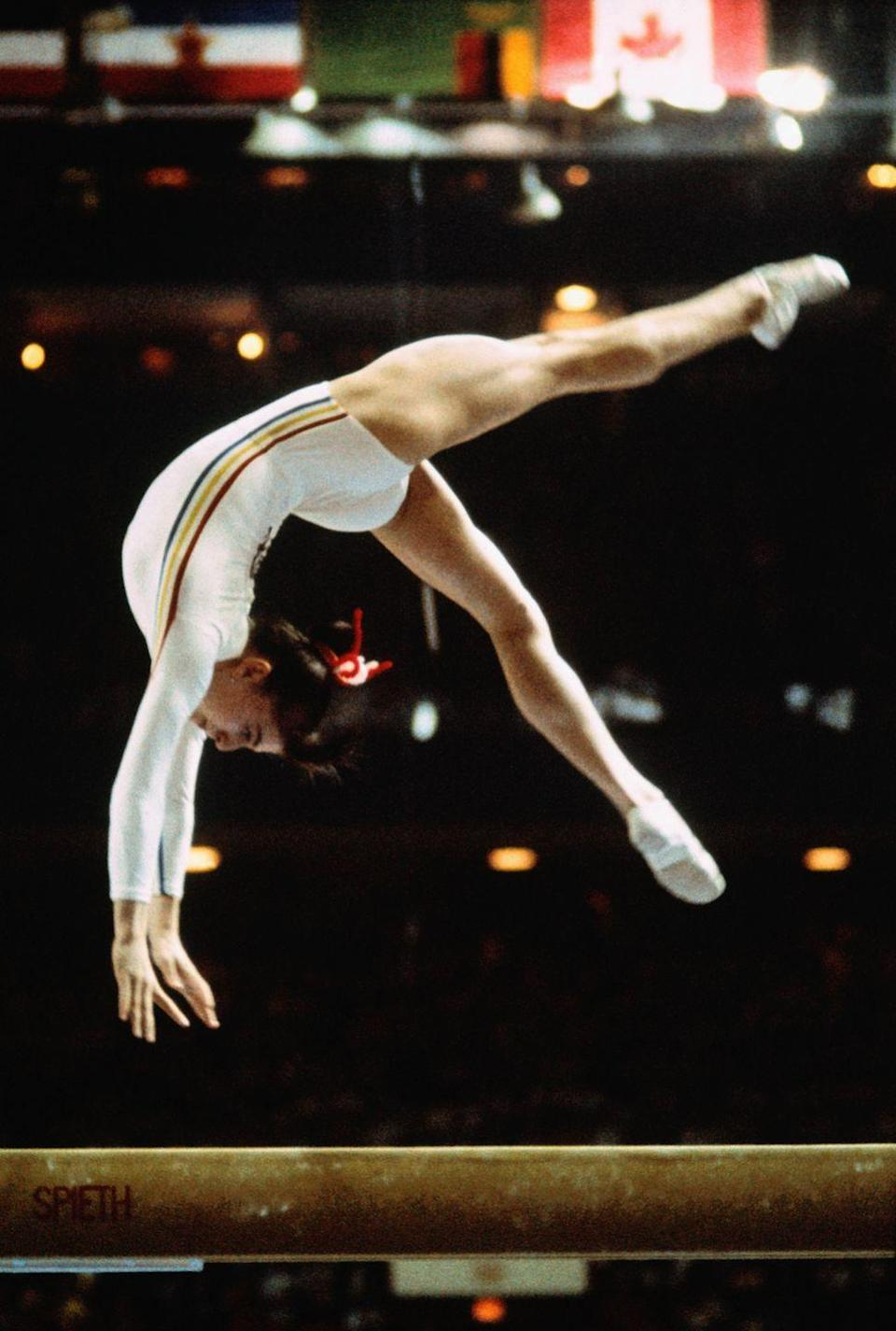 """<p>At just 14 years old, Nadia Comăneci took home the gold medal for her routine on the uneven bars. However, it was her <a href=""""https://olympics.com/en/video/first-perfect-ten-nadia-comaneci#:~:text=In%201976%20in%20Montreal%2C%20Romanian,performance%20on%20the%20uneven%20bars."""" rel=""""nofollow noopener"""" target=""""_blank"""" data-ylk=""""slk:score of 10.0"""" class=""""link rapid-noclick-resp"""">score of 10.0</a> that caught people's attention. The Romanian athlete became the first gymnast in Olympic history to receive a perfect score. </p>"""