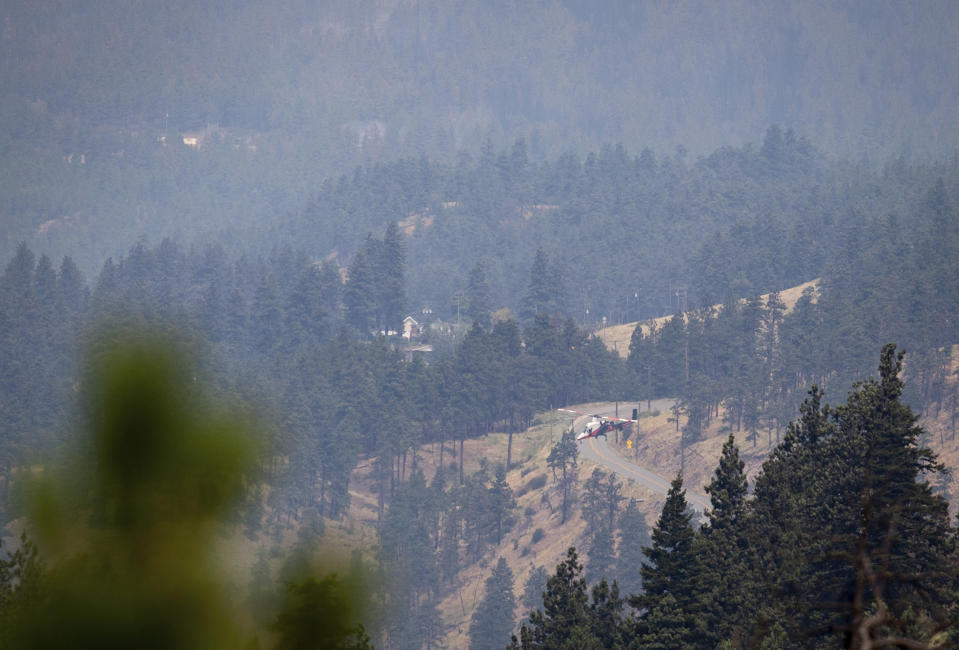 A helicopter pilot descends to pick up water while battling a wildfire burning in Lytton, British Columbia, Friday, July 2, 2021. Officials on Friday hunted for any missing residents of a British Columbia town destroyed by wildfire as Canadian Prime Minister Justin Trudeau offered federal assistance. (Darryl Dyck/The Canadian Press via AP)