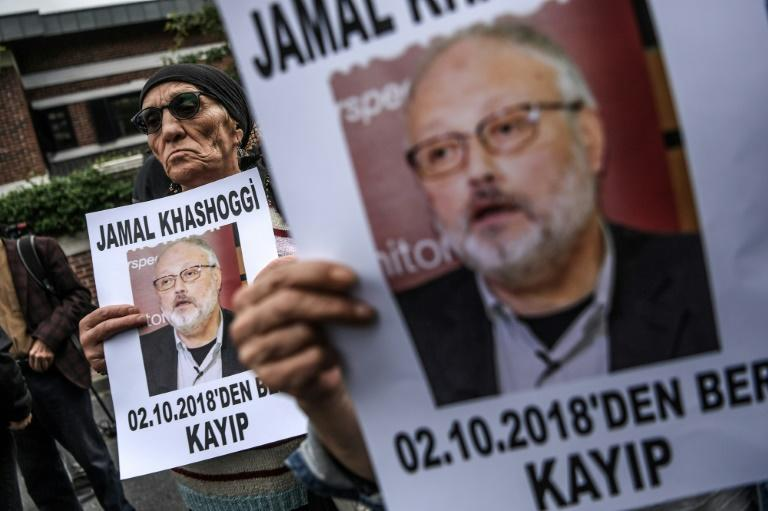 "A file photo taken on October 9, 2018 shows protesters holding portraits of missing Riyadh critic Jamal Khashoggi with the caption: ""Jamal Khashoggi is missing since October 2"" during a demonstration in front of the Saudi Arabian consulate"