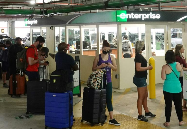People wait in line at an Enterprise rental agency at Miami International Airport in April 2021