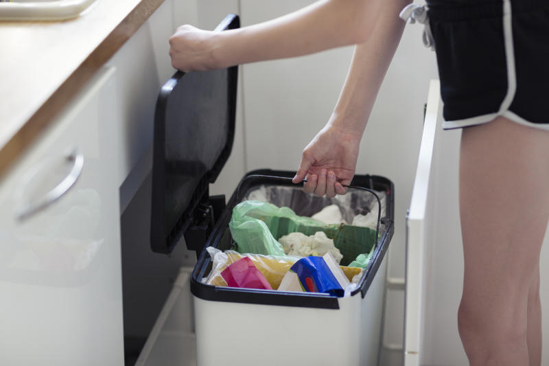 Pictured is a woman emptying a bin in her kitchen.