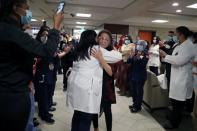 Intensive Care Unit Nurse Merlin Pambuan, is hugged by hospital staff as she walks out of the hospital in Long Beach