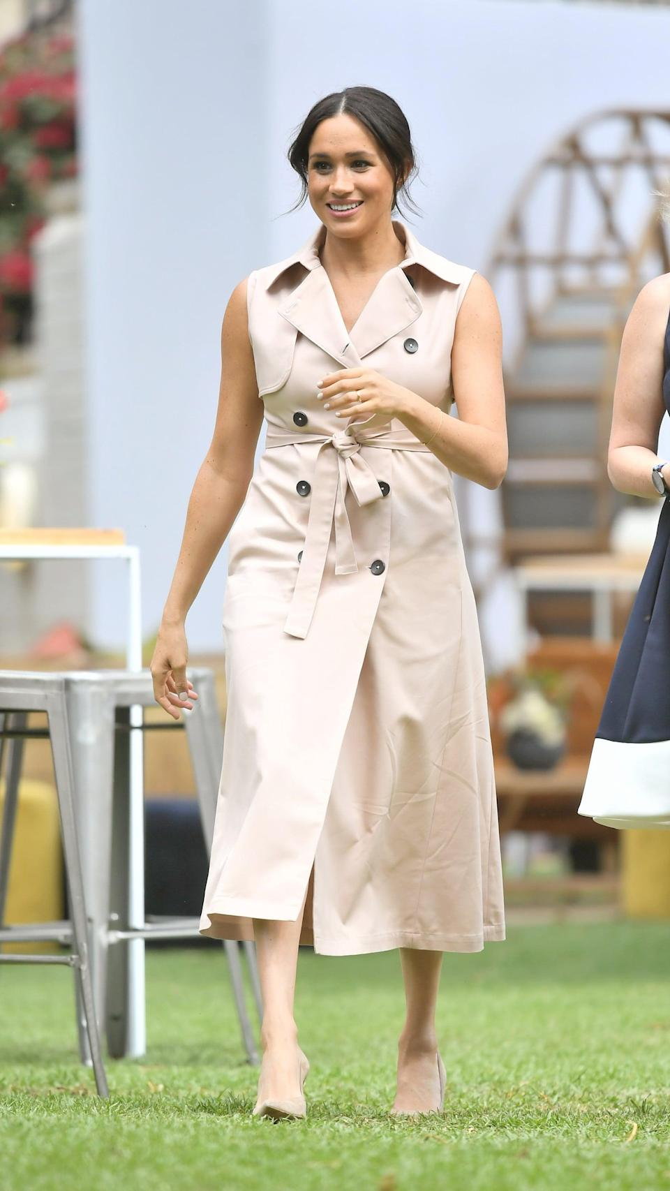 """<p>Meghan <a href=""""https://www.popsugar.co.uk/fashion/photo-gallery/46669039/image/46747379/Meghan-Duchess-Sussex-Wearing-Beige-Sleeveless-Belted-Trench-Dress"""" class=""""link rapid-noclick-resp"""" rel=""""nofollow noopener"""" target=""""_blank"""" data-ylk=""""slk:rewore this winning Nonie trench dress"""">rewore this winning Nonie trench dress</a> during her royal tour of Southern Africa the following year. </p>"""