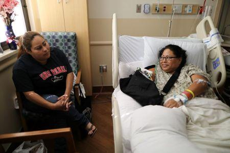 Paola Bautista, 39, from Fontana, California, (R) sits in her hospital bed next to her sister Daisy Bautista at Sunrise Hospital & Medical Center after being shot at the Route 91 music festival mass shooting next to the Mandalay Bay Resort and Casino in Las Vegas, Nevada, U.S. October 4, 2017. Picture taken October 4, 2017. REUTERS/Lucy Nicholson