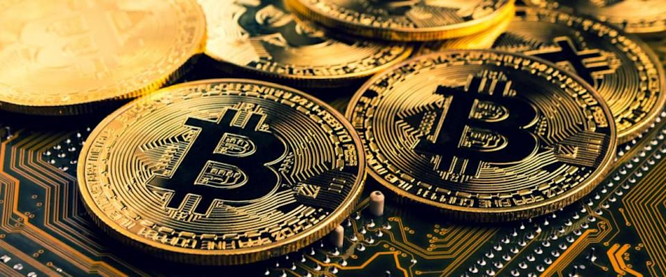 Golden coins with bitcoin symbol on a motherboard.