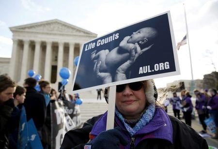 A protester holds up a sign in front of the U.S. Supreme Court on the morning the court takes up a major abortion case focusing on whether a Texas law that imposes strict regulations on abortion doctors and clinic buildings interferes with the constitutional right of a woman to end her pregnancy, in Washington March 2, 2016.  REUTERS/Kevin Lamarque/File Photo