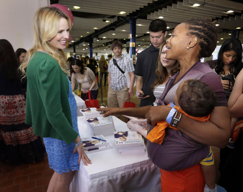 """This May 18, 2013 photo shows pregnancy advise guru Rosie Pope, center, speaking with attendees at the New York Baby Show in New York. Pope is the author of the pregnancy guide, """"Mommy IQ,"""" and also has her own maternity clothing line. (AP Photo/Richard Drew, file)"""