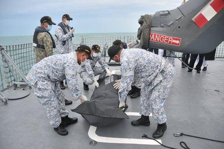 Royal Malaysian Navy personnel carry a body onto their ship during a search and rescue operation for survivors of the USS John McCain ship collision in Malaysian waters in this undated handout released August 22, 2017. Royal Malaysian Navy Handout via REUTERS
