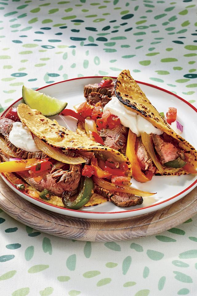 """<p><b>Recipe: <a href=""""https://www.southernliving.com/recipes/easy-steak-fajitas"""">Easy Steak Fajitas</a></b></p> <p>Pick up a container of freshly sliced onions and bell peppers at the grocery store to save time (and tears) when preparing the fajitas. We prefer fresh over frozen vegetables in this recipe; they stay firmer when cooked. Let everyone customize their fajitas by setting out an assortment of toppings such as fresh cilantro, guacamole, salsa, and sour cream.</p>"""