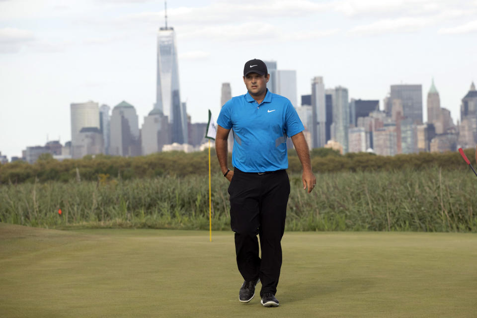 With the New York skyline in the distance, Patrick Reed walks off the 15th green at the Northern Trust golf tournament at Liberty National Golf Course, Sunday, Aug. 11, 2019, in Jersey City, N.J. Reed won the tournament. (AP Photo/Mark Lennihan)