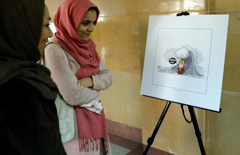 """Iranians look at illustrations during the """"Persian Gulf Forever"""" cartoon exhibition in Tehran on October 18, 2017"""